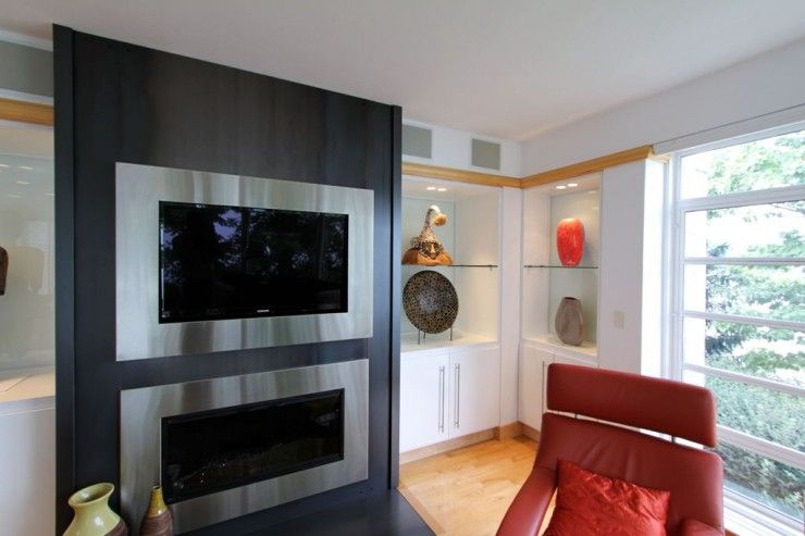 black wall, stainless framed tv and fireplace