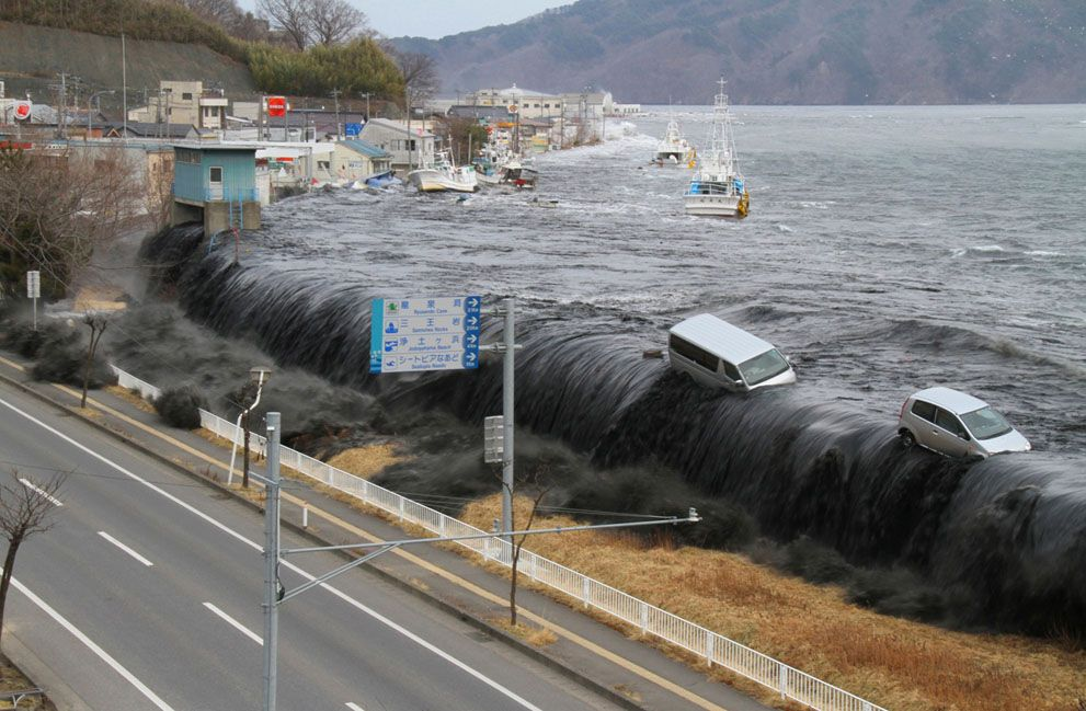 Tsunami Waves overflow a coastal barrier in Japan March 2011 ...