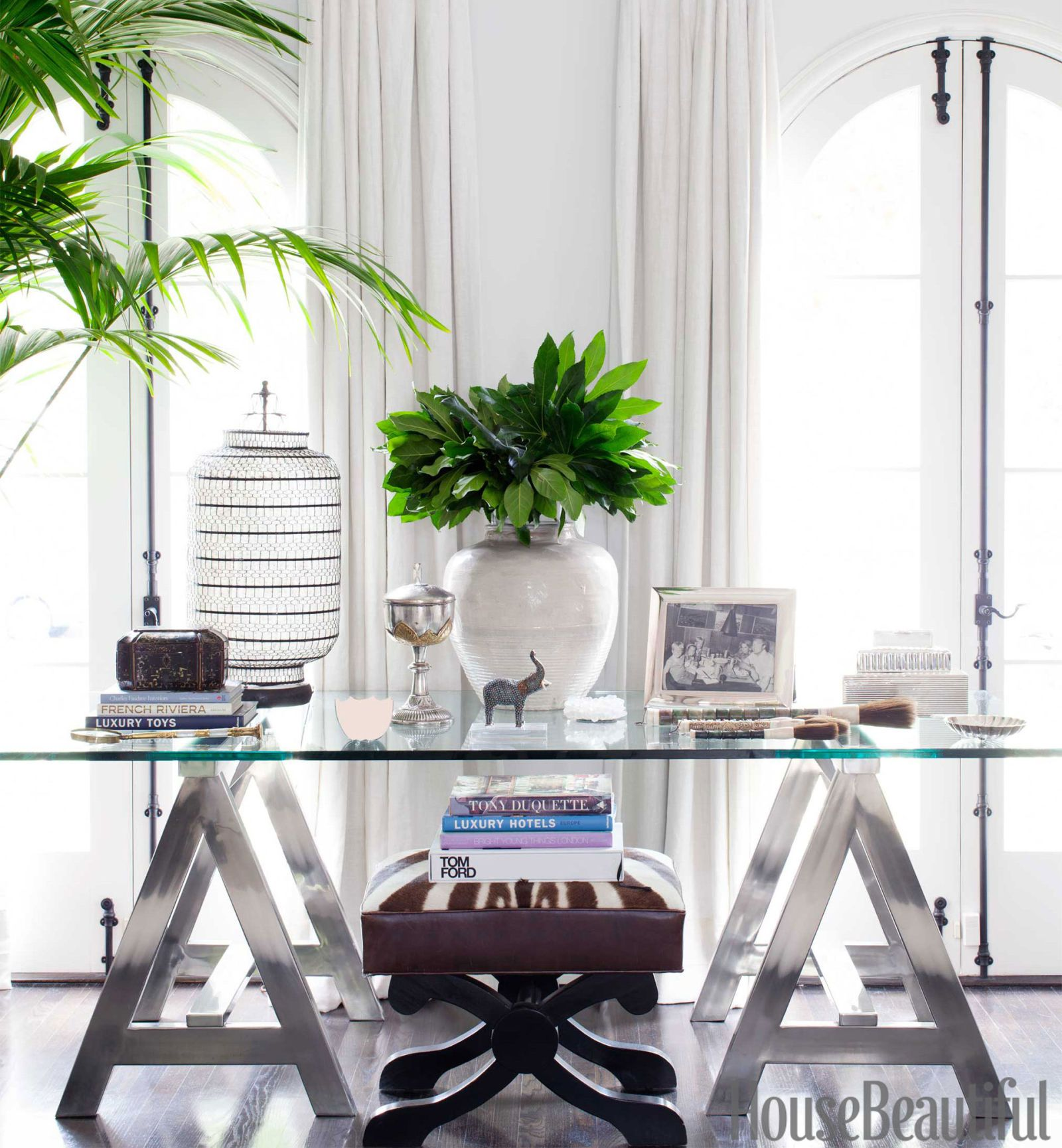 A California-style tableau in the light-filled living room: A chrome-and-glass sawhorse table by Ralph Lauren Home holds collected objects, including an antique white vase from Oriental Treasures; the bench is by Jan Showers. - HouseBeautiful.com