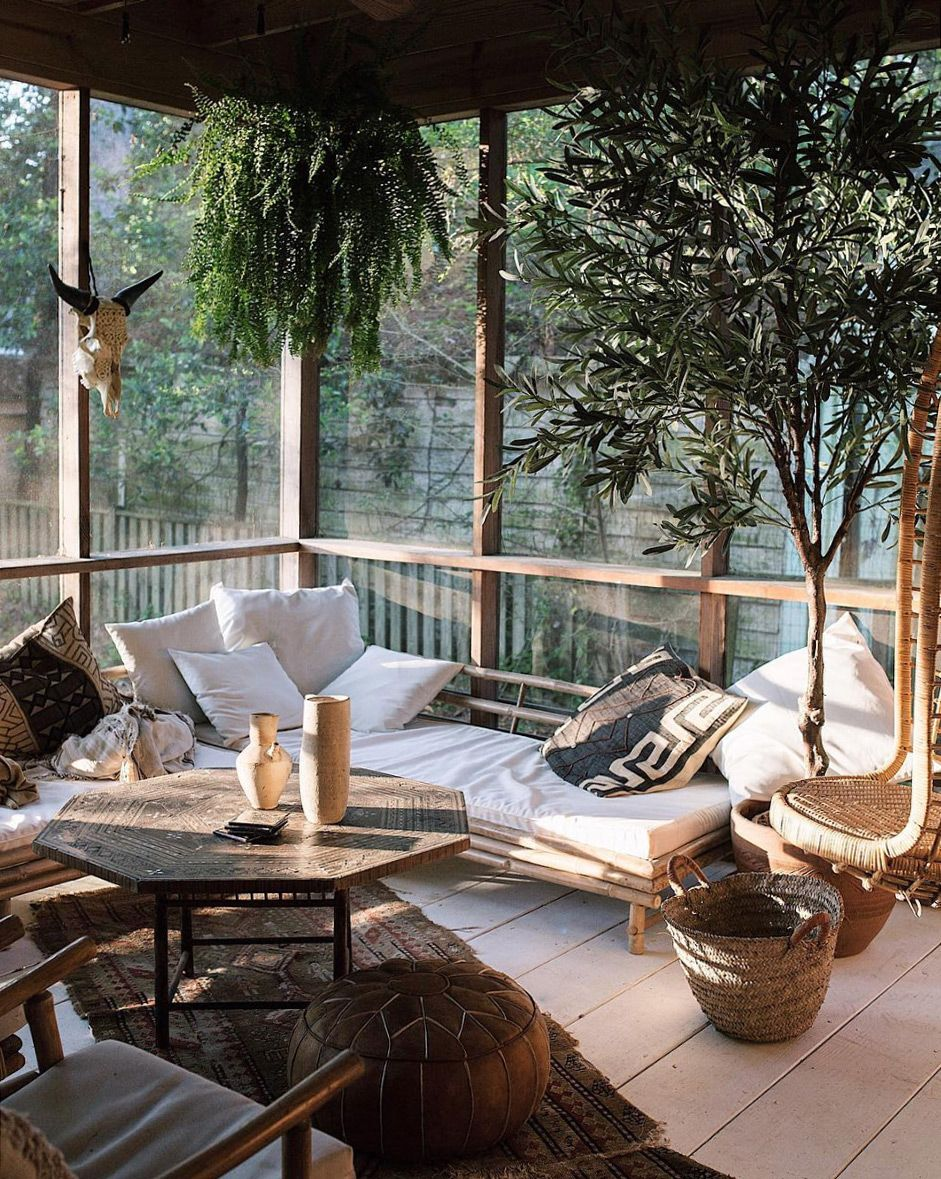 sunroom with green houseplants and white linen daybed