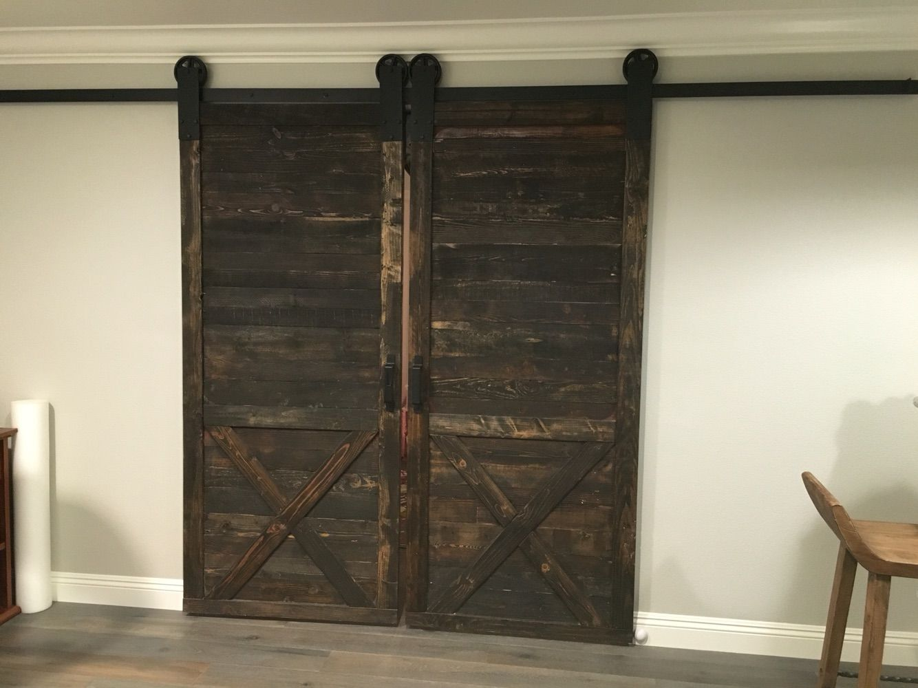 Dark Stained Rustic Sliding Barn Doors With X Bracing Located In