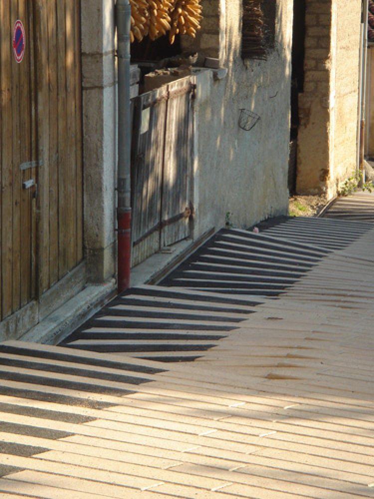 El aparejo de las piezas del pavimento se despliega en superficies regladas que ponen en contacto la pendiente de una rampa con el umbral de acceso a cada vivienda.