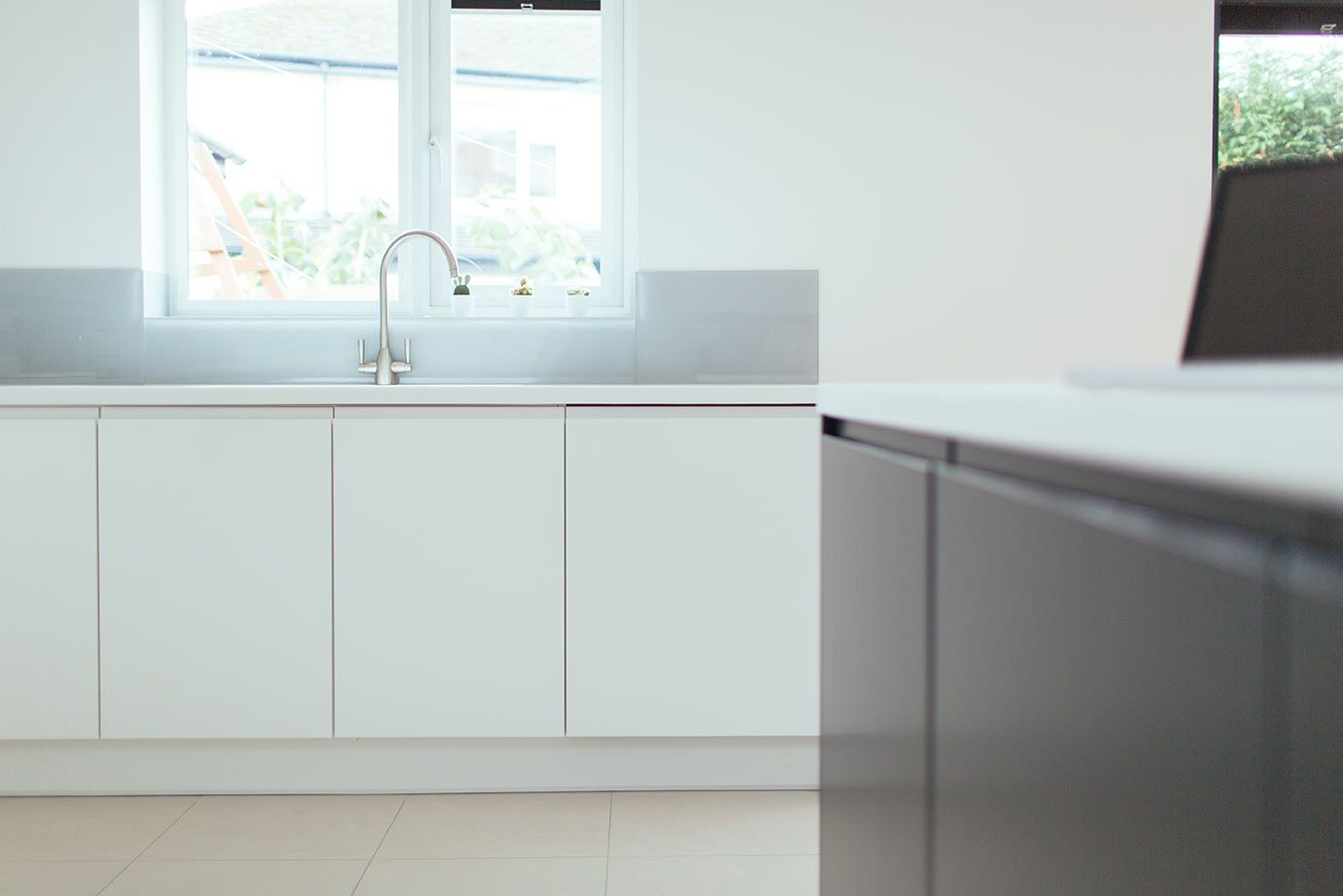 White Kitchen Grey Splashback matt white kitchen. matt grey kitchen. corian worktop. grey