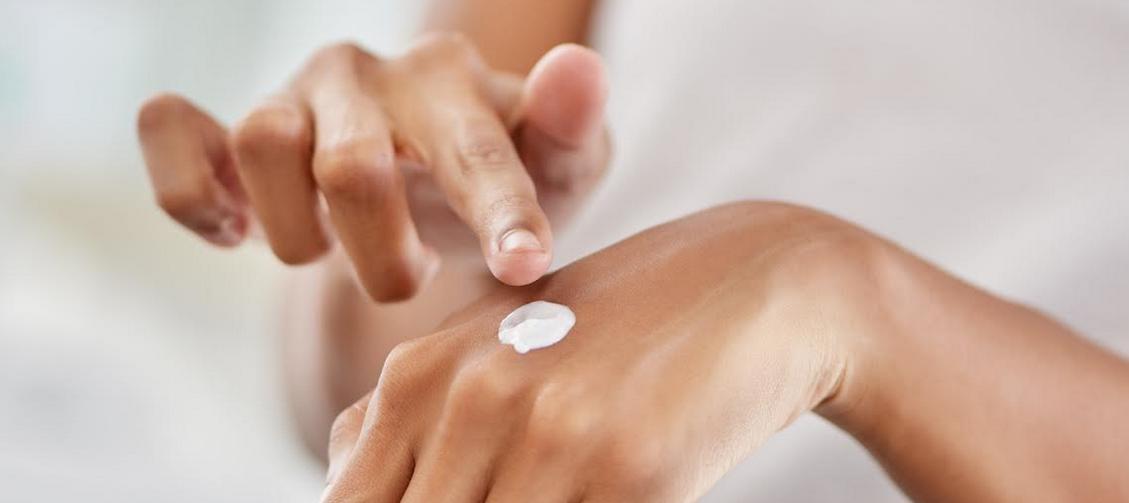 unos dedos aplicando crema sobre el dorso de la otra mano
