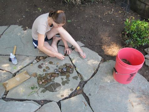 Filling The Gaps Between Flagstones With Pebbles.