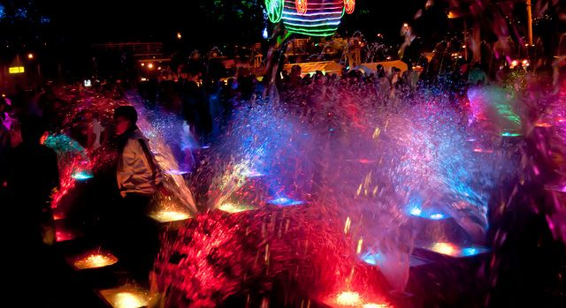 As Medellin, Colombia has summer during the Christmas season, kids run through colorful water fountains at the Christmas light display.
