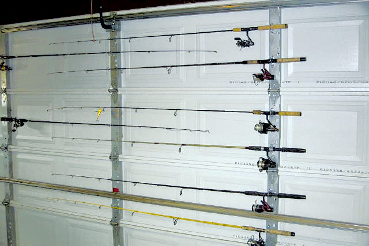 Fishing rod storage on garage door uses u bolts to hold for Fishing rod organizer