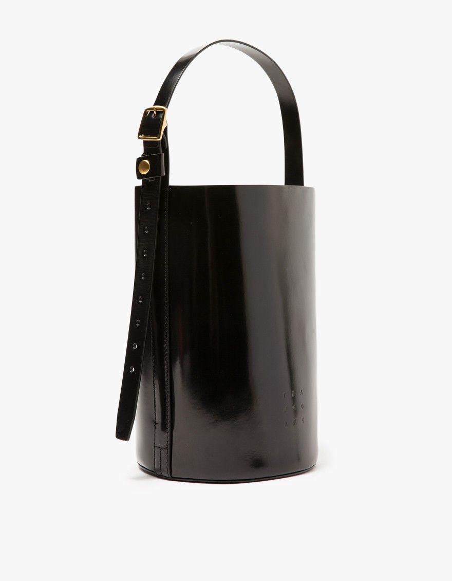 From Trademark, a structured leather bucket bag in Black with minimalist styling. Features single adjustable shoulder strap, pressed front logo, flat bottom and gold tone hardware.   •Leather bucket bag in Black •Single adjustable shoulder strap •G