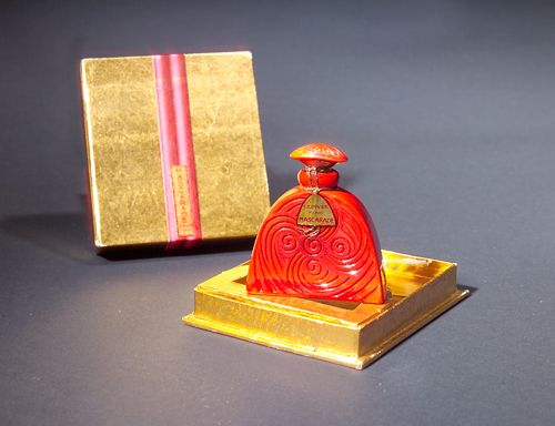"""""""Mascarade,"""" a DEPINOIX perfume bottle for Piver, circa 1927, in opaque red glass, with gilt recesses, with label, sealed in box. Ht. 2"""""""