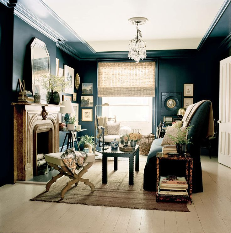 dark and glamorous sitting room with blue-black walls contrasting ...