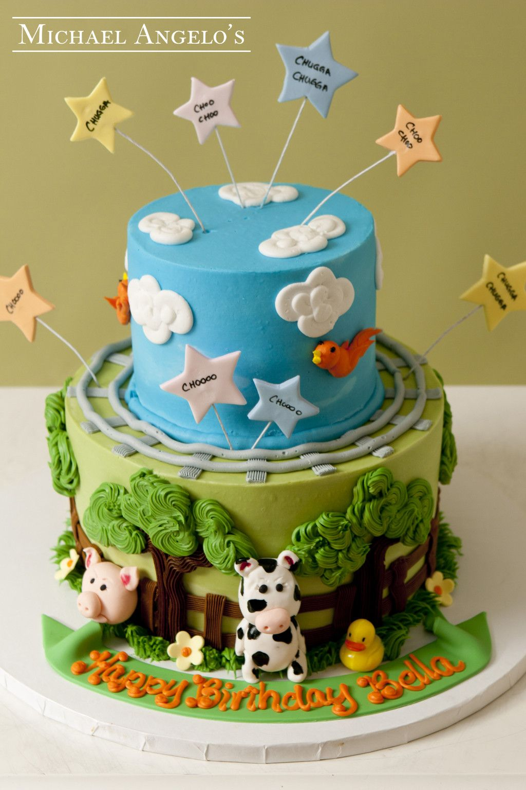 Blue Skies & Animals #24Animals  This creative design is iced in fondant with special decor all around for a farm scene with animals and blue skies. The cow and pig are hand made from gum paste along with the fence and railroad. The star cut-outs that stick out from the cake bring some depth and make it look really festive.