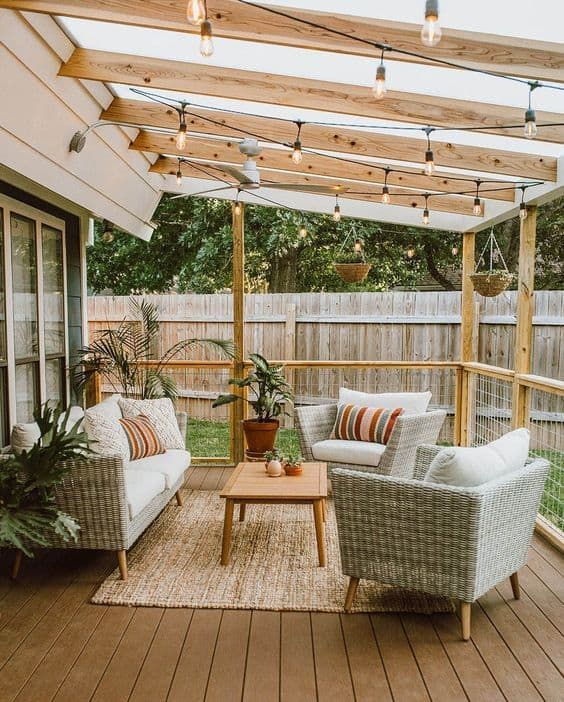 Patio decorated with plants and white shade furniture and surrounded with bare enclosure made of wood and metal