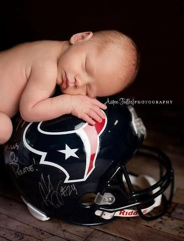 Newborn baby sleeping on top of football helmet