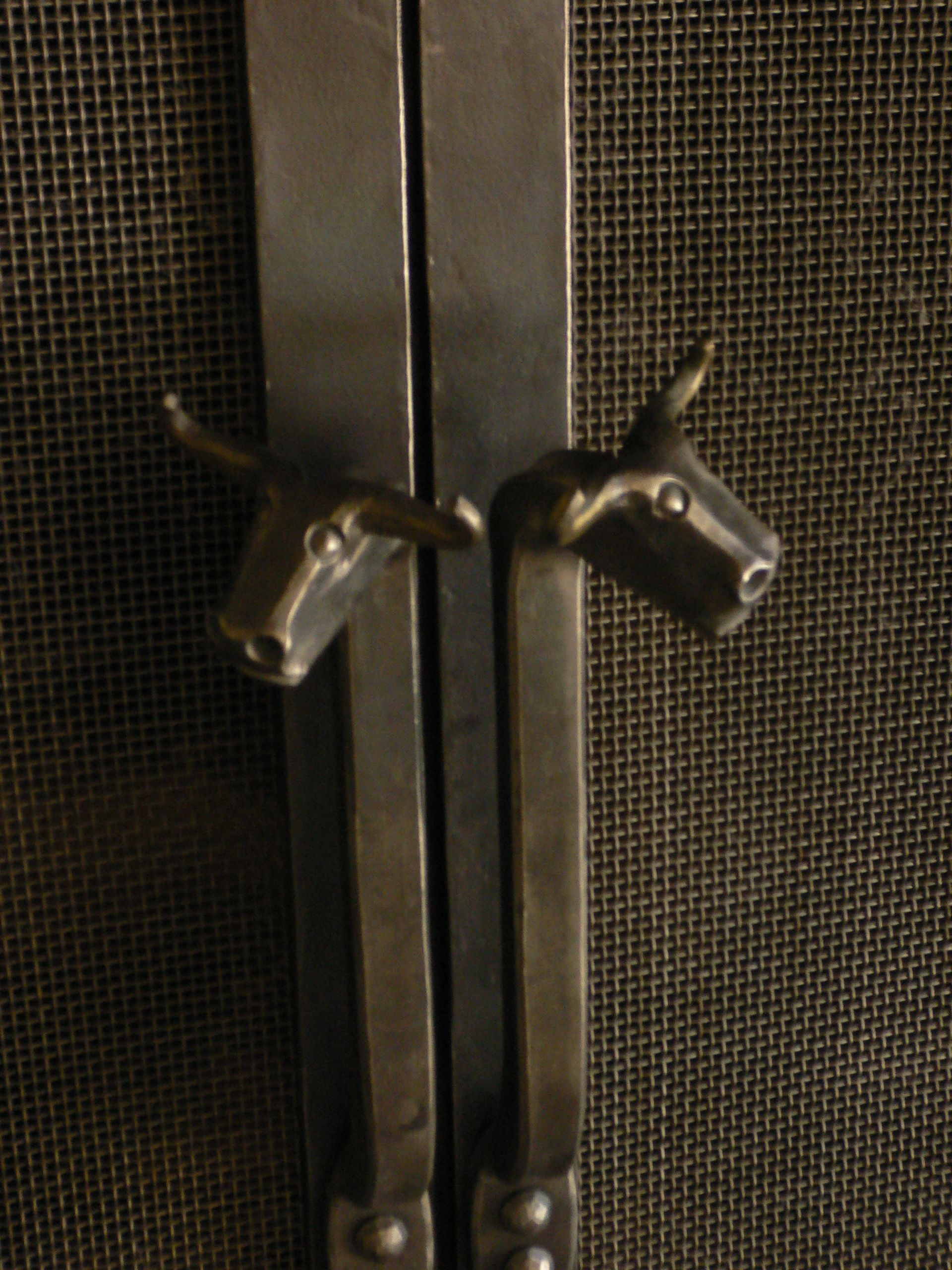 blacksmith forged iron door handles on the fireplace bull heads