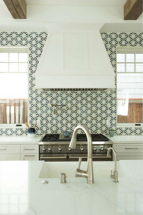 Windows Flank A White Wood Range Hood Mounted To Black And Mosaic Wall Tiles Over Stainless Steel Oven Positioned Between Shaker