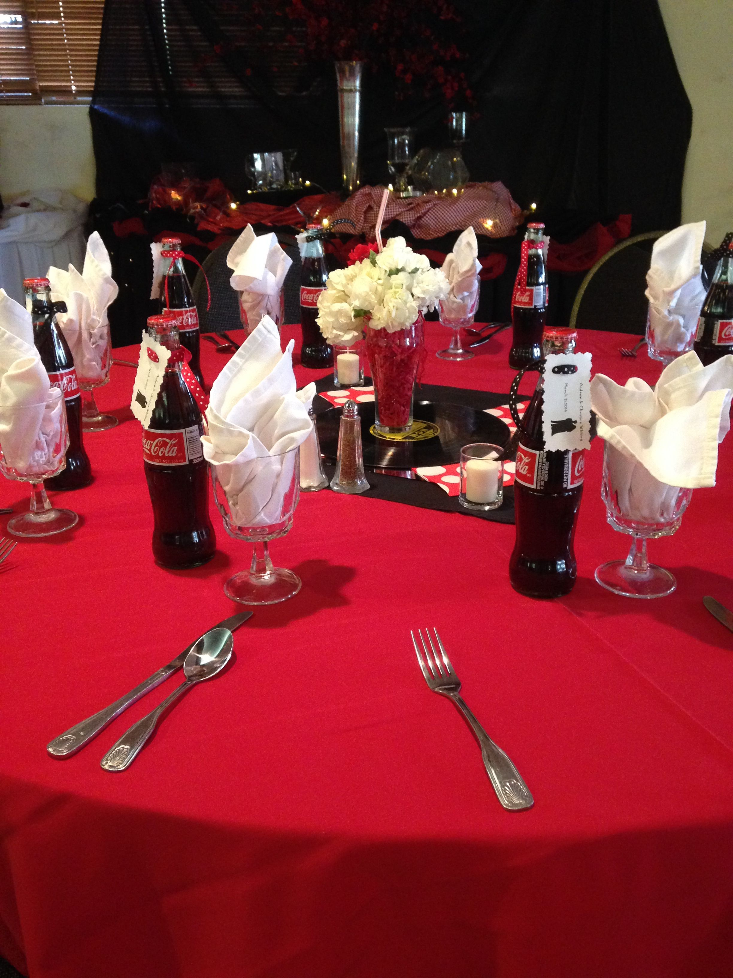 Table Set Up With Coca Cola Party Favors For A 50s Themed Wedding