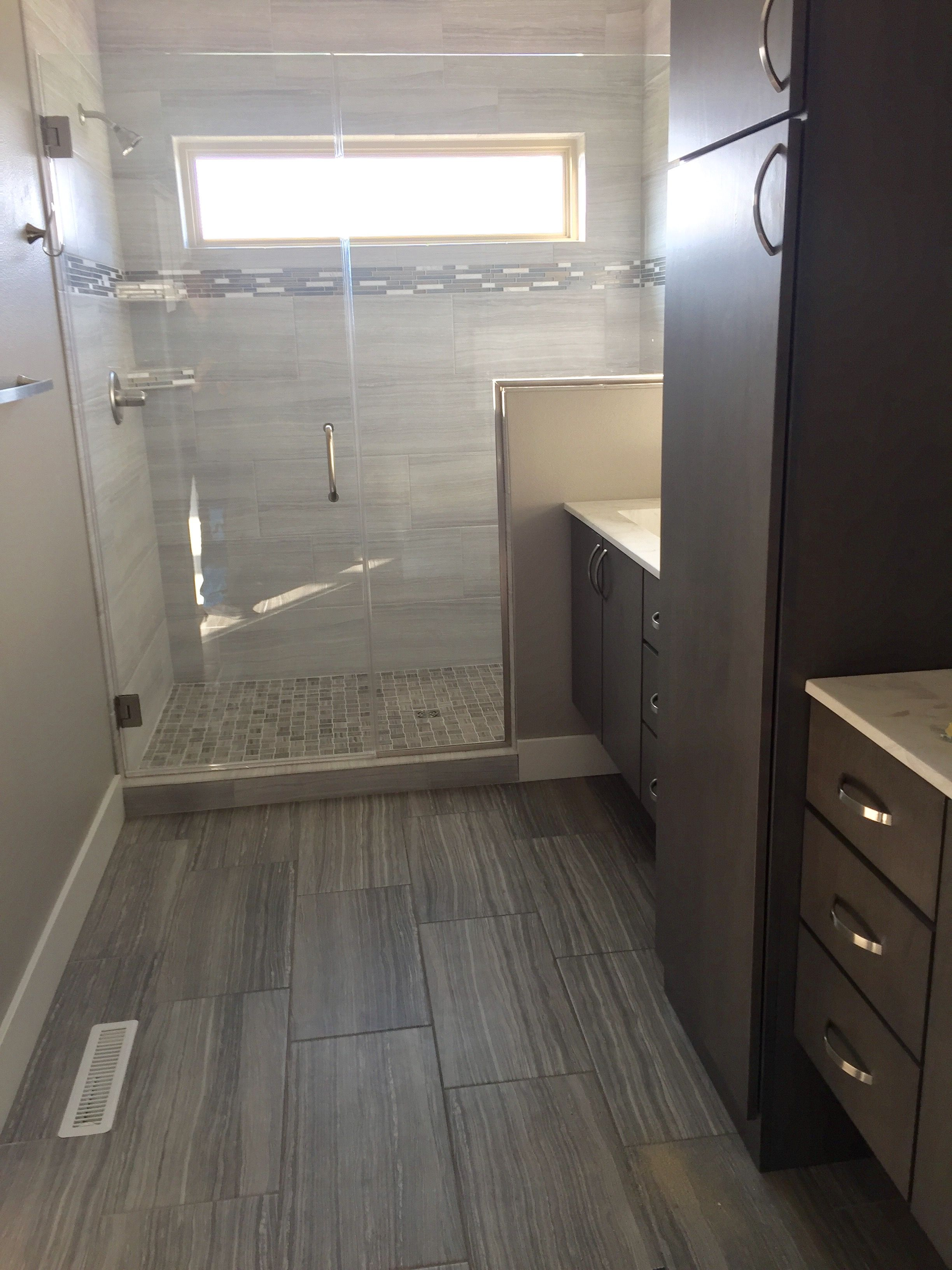 Dark gray 12x24 floor tile transitioning into a light white gray