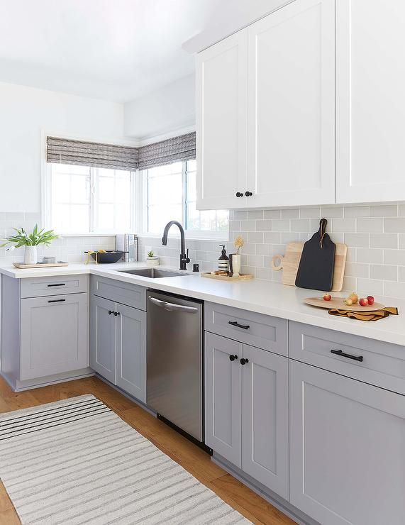 A gray stripe runner sits in front of a stainless steel dishwasher fitted between gray shaker cabinets donning matte black pulls and a white quartz countertop fixed against light gray subway tiles. #whiteshakercabinets