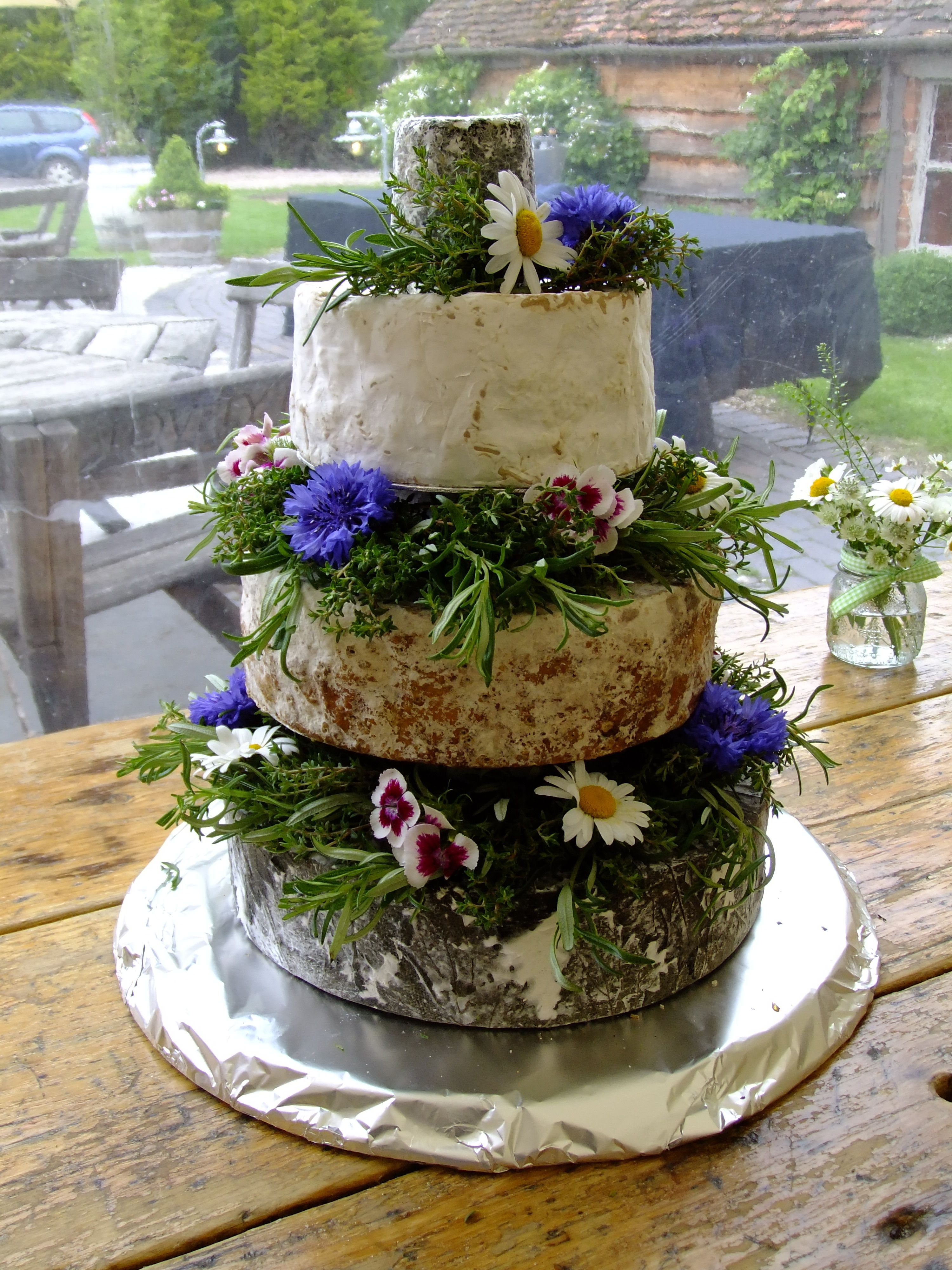 Cheese wedding cake decorated with edible fresh flowers