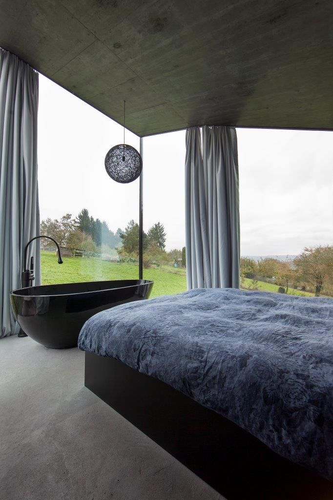 Freistehende Badewanne im Schlafzimmer mit Tageslicht