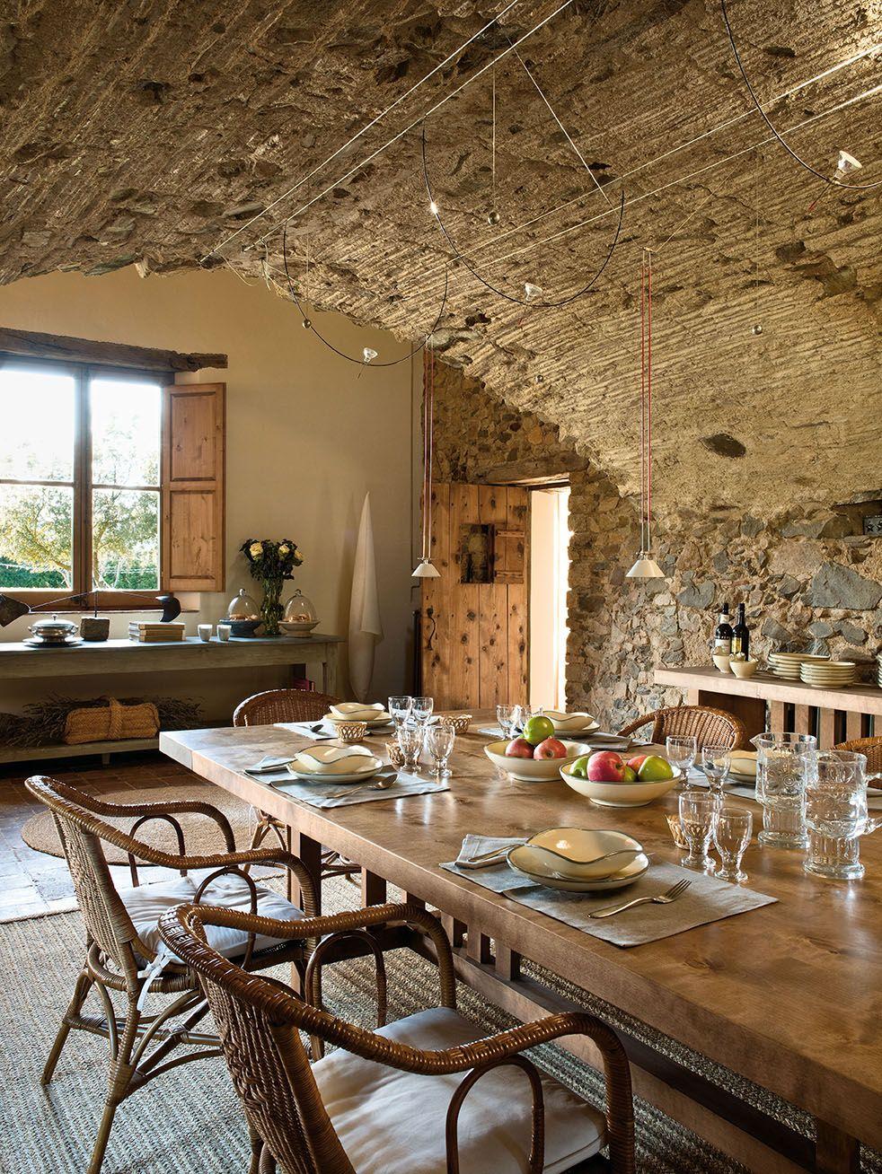 Comedor con paredes de piedra, mesa de madera y sillas de ...