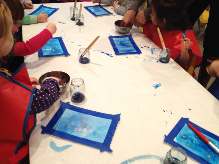 Toddler class creating watercolor star sticker resist paintings inspired by how to catch a star