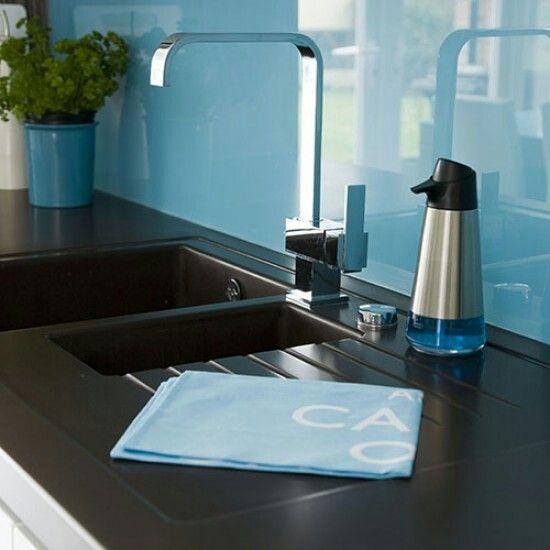 Black sink and worktop with blue glass splashback A kitchen sink ...