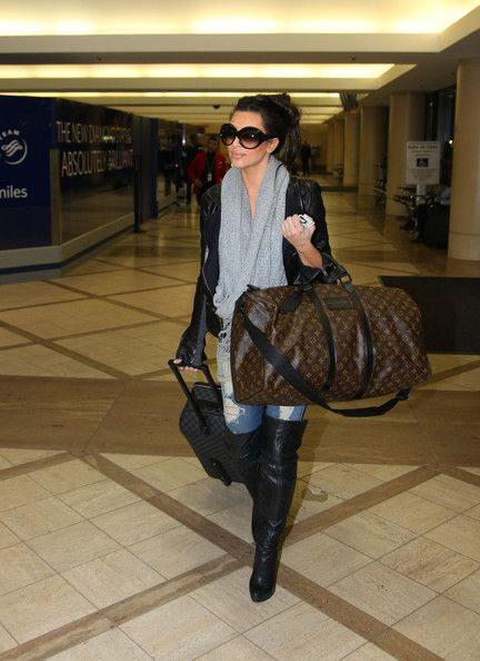 0f4444a00413 Miss Kardashian displayed her love of Louis Vuitton while traveling through  LAX. Strutting her stuff in a pair of knee-high-leather boots she carried a  huge ...