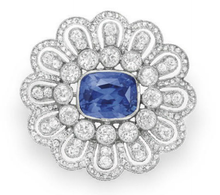 A BELLE EPOQUE SAPPHIRE AND DIAMOND BROOCH Bezel-set with a cushion-cut sapphire, within a collet-set diamond surround, to the rose and old European-cut diamond foliate motif frame, mounted in platinum, circa 1910
