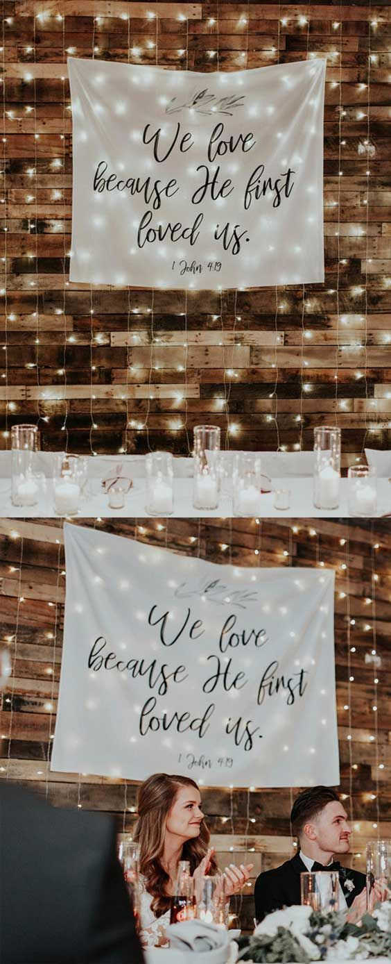 Photo of We Love Because He First Loved Us | Christian Wedding Bible Verse Backdrop Decorations