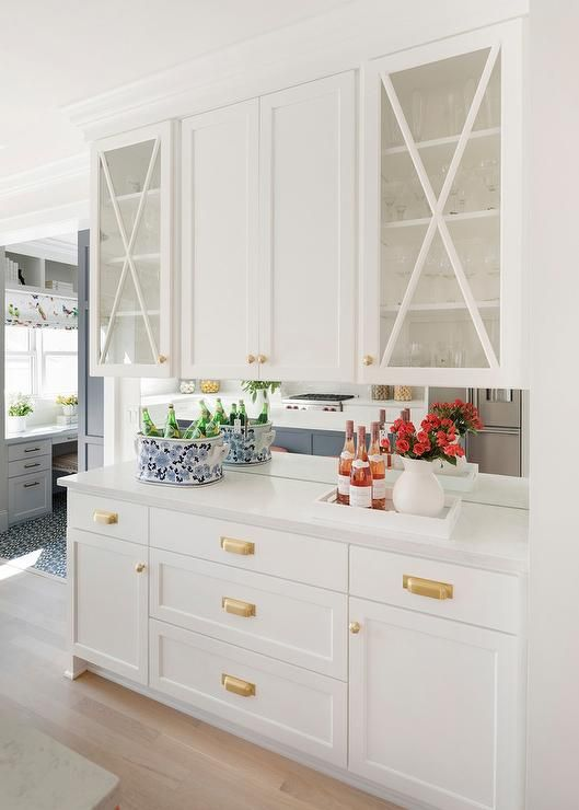 Glass front mullion cabinets flank white shaker cabinets donning gold knobs and are fitted over white shaker drawers accented with brass hardware and a white quartz countertop fixed against a mirrored backsplash. #whiteshakercabinets