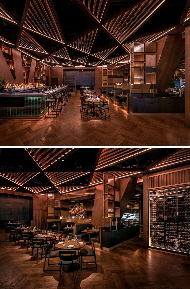 This modern restaurant's distinctive and massive structural joists divide the bar area from the main dining room. These angled columns& inspired the bar's geometrical millwork and its triangular patterned wood trellis ceiling. #RestaurantDesign #ModernRestaurant #RestaurantInterior