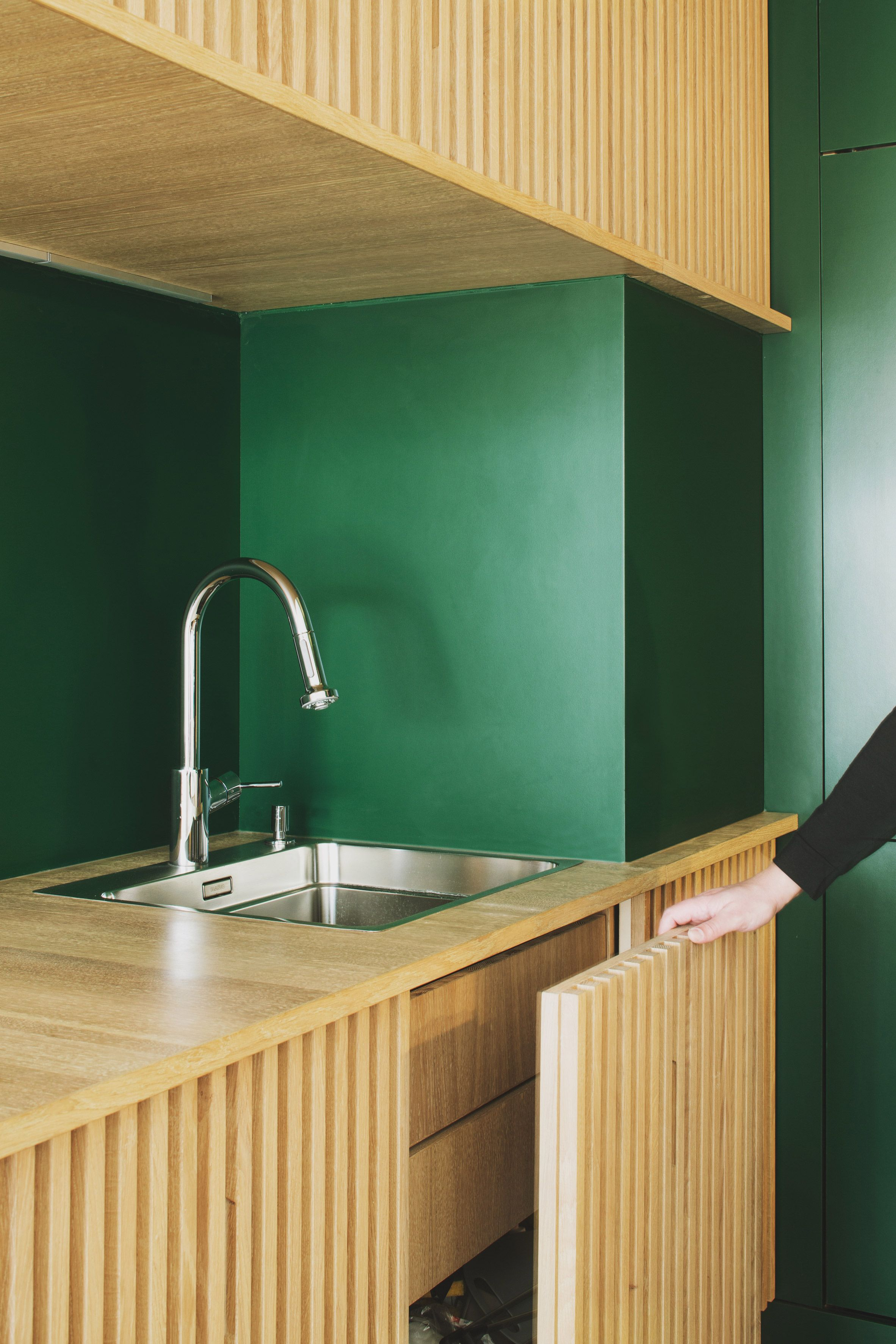 A Pair Of Grooved Oakwood Volumes That Contain Extra Cupboards Have Been Inserted On One Side O Interior Design Kitchen Paris Apartment Interiors Green Kitchen