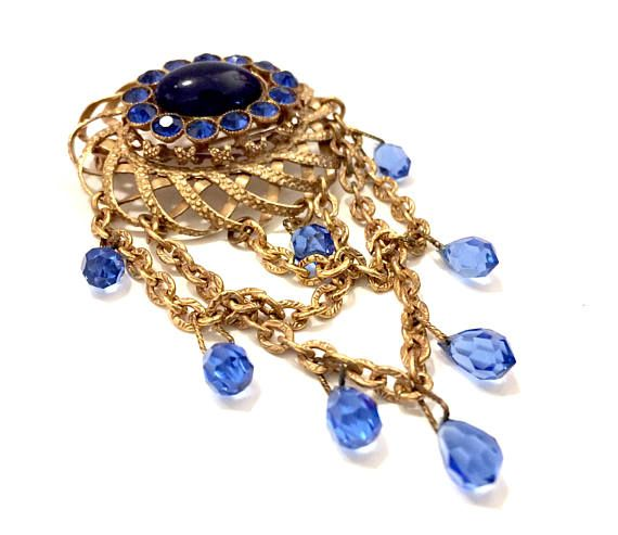 Victorian Revival Blue & Gold Large Brooch  Measures: Approx. 4L x 2W  Mark: None  Condition: Very Good vintage condition  Beautiful statement brooch composed of textured and smooth gold tone metal. Stunning cascading design of gold tone chain accented with beautiful blue briolite crystal drops. Weaved open work domed centerpiece with a striking oval deep blue cabochon that is framed with sapphire blue chaton rhinestones. This is a large and dramatic vintage brooch win a ton of texture, d...