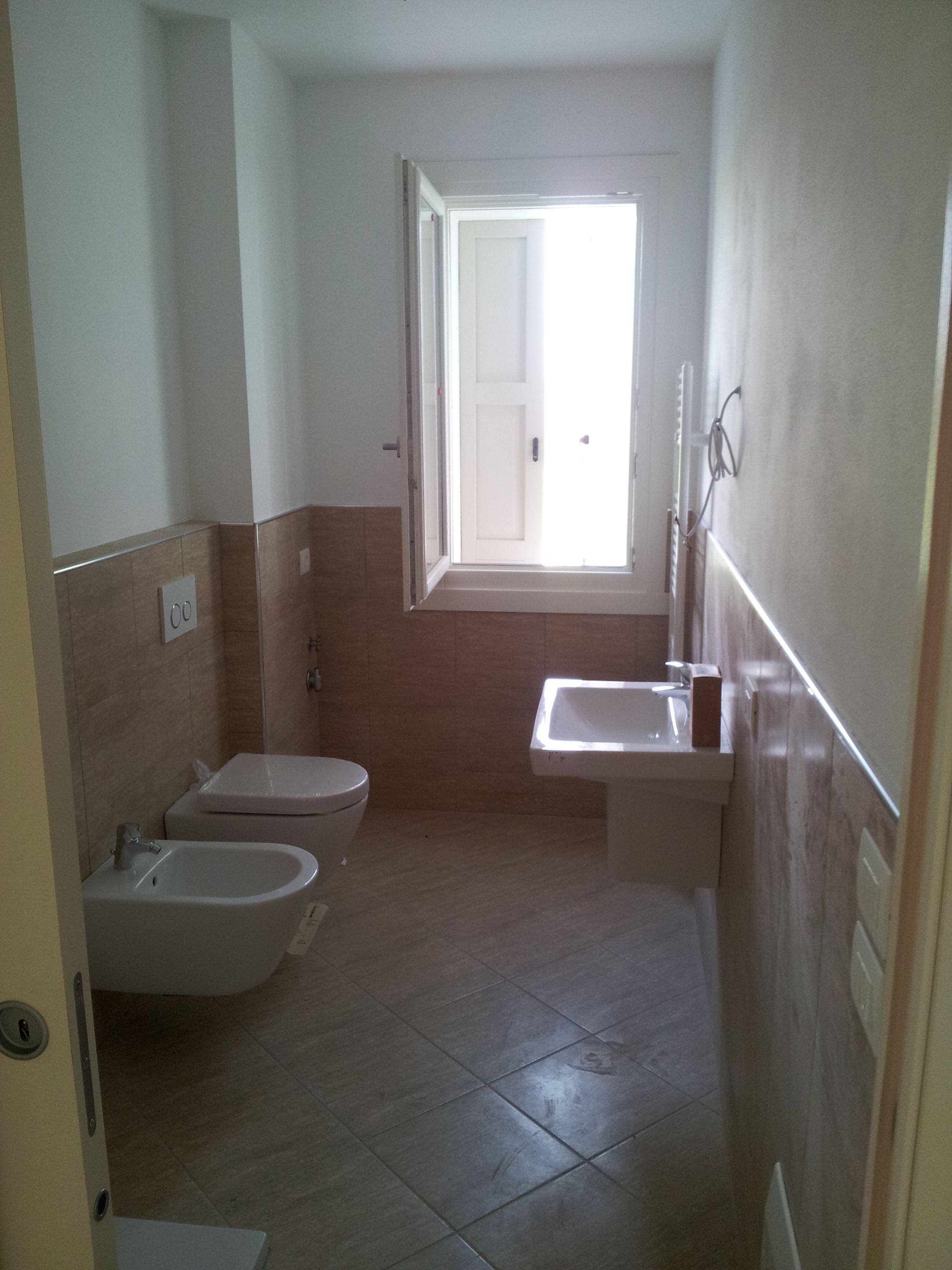 Bagno con sanitari bianchi, pavimento e rivestimento uguali che ...