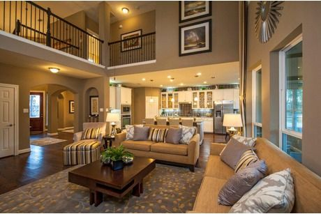 A balcony overlooks a two story great room and adjoining for Living room balcony design