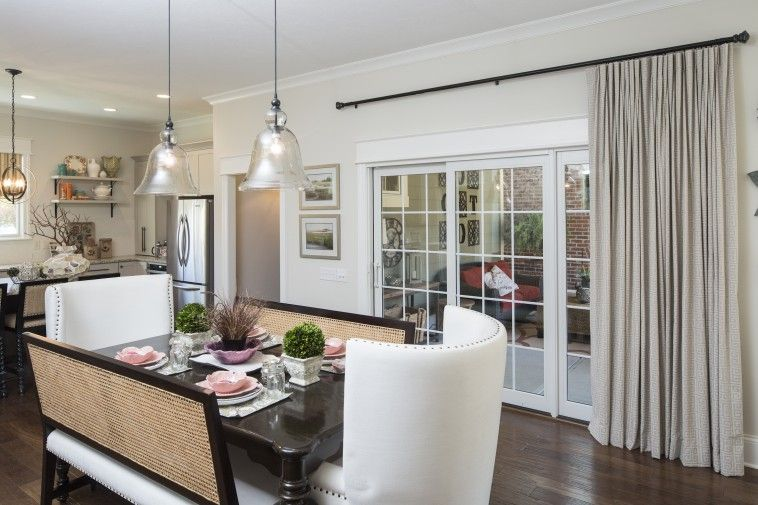 Dining Room With Sliding Glass Door Having Cream Curtain Hanging On Black Iron Rods And White