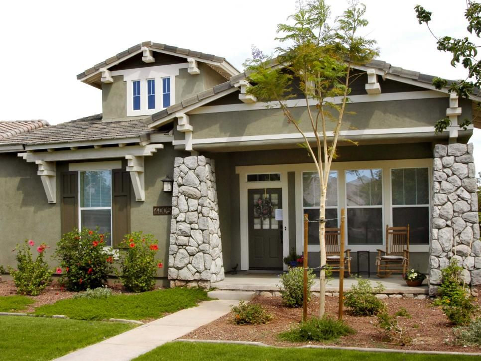 Green stucco siding and brown shutters create an earthy for Craftsman home windows