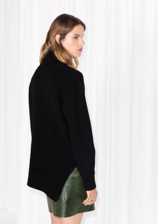 Knitted from a soft wool blend, this soft sweater has an asymmetric hem and a cozy turtle neck.