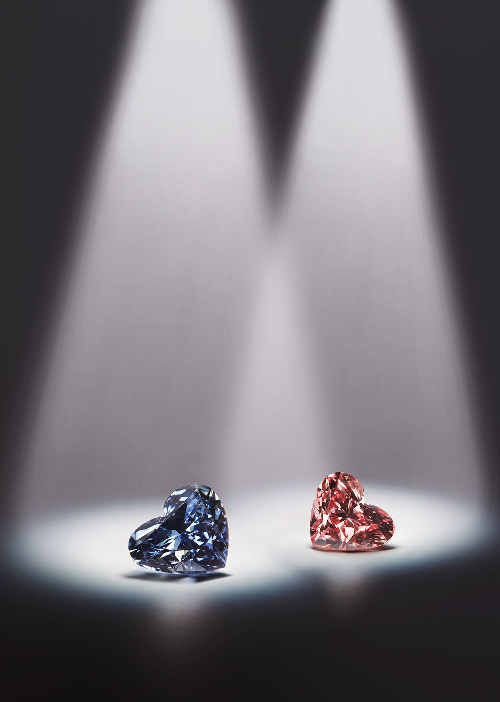 Two heart-cut diamonds from the Argyle Pink Diamonds Tenders 2013 in Tokyo: the 0.71ct Argyle Celestial Fancy Dark Gray-Blue diamond (left) and a matching pink diamond heart.