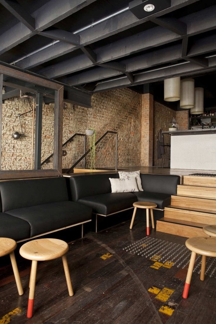 Exposed brick walls reclaimed wood floors three legged stools black leather banquette seating insuper whatnot in brisbane australia marc and co