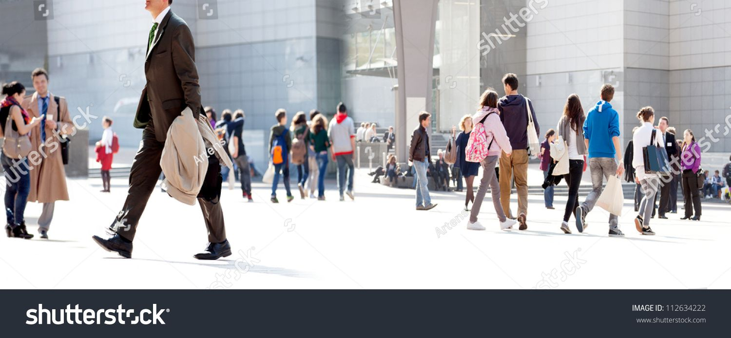 People Walking Against The Light Background Of An Urban Landscape