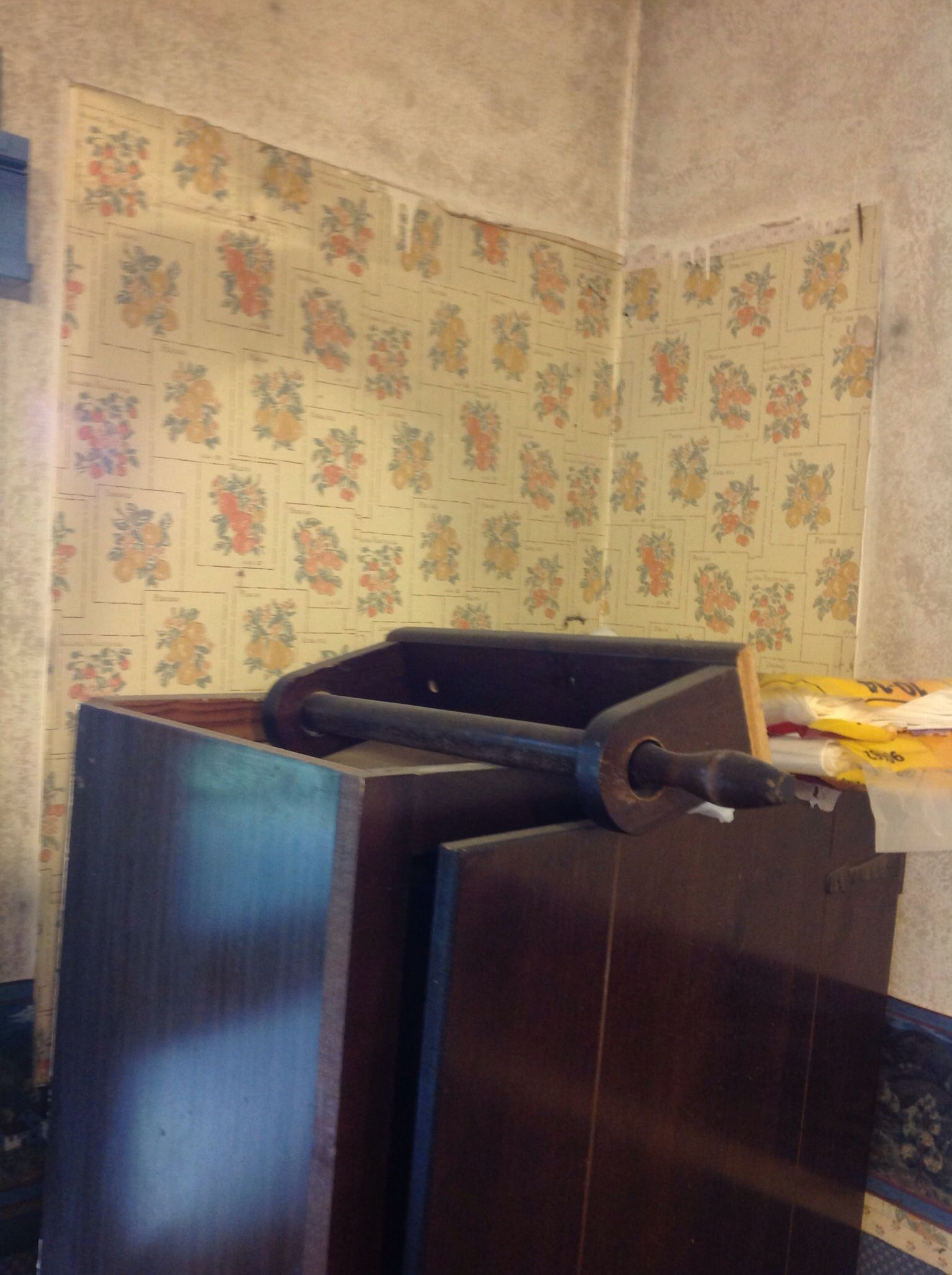 Cabinets coming down revealed house wallpaper history.