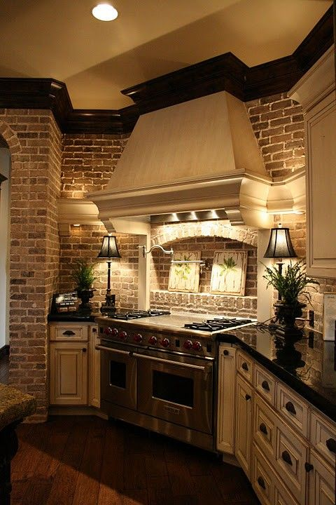 Such a comfy kitchen! Like the Hood.  love the brick and soft lighting.