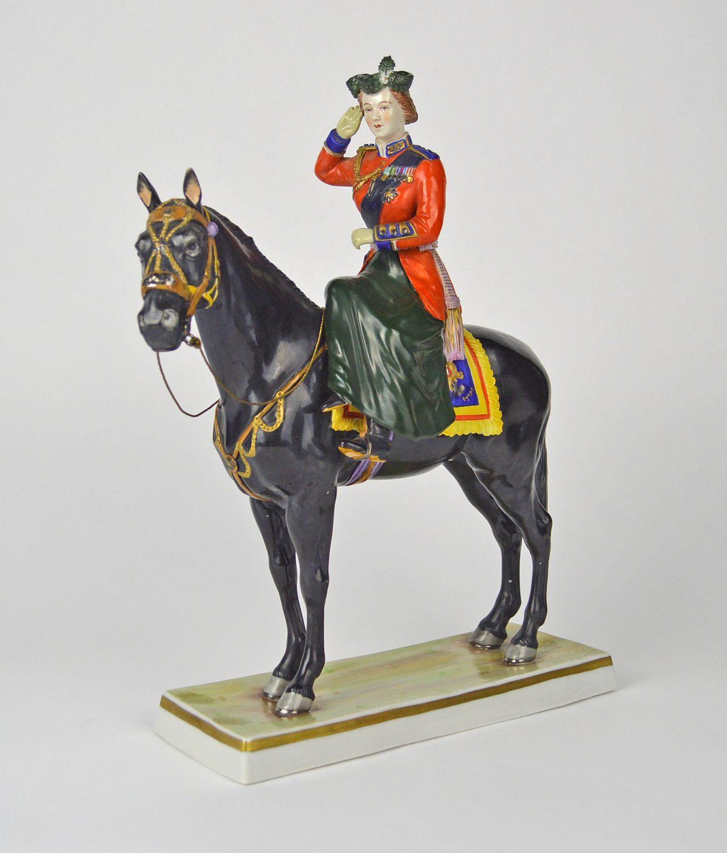A German Sitzendorf porcelain figure of Queen Elizabeth II on horseback riding side-saddle and saluting, with gilt highlights on rectangular base, underglaze blue factory mark, 36cm high