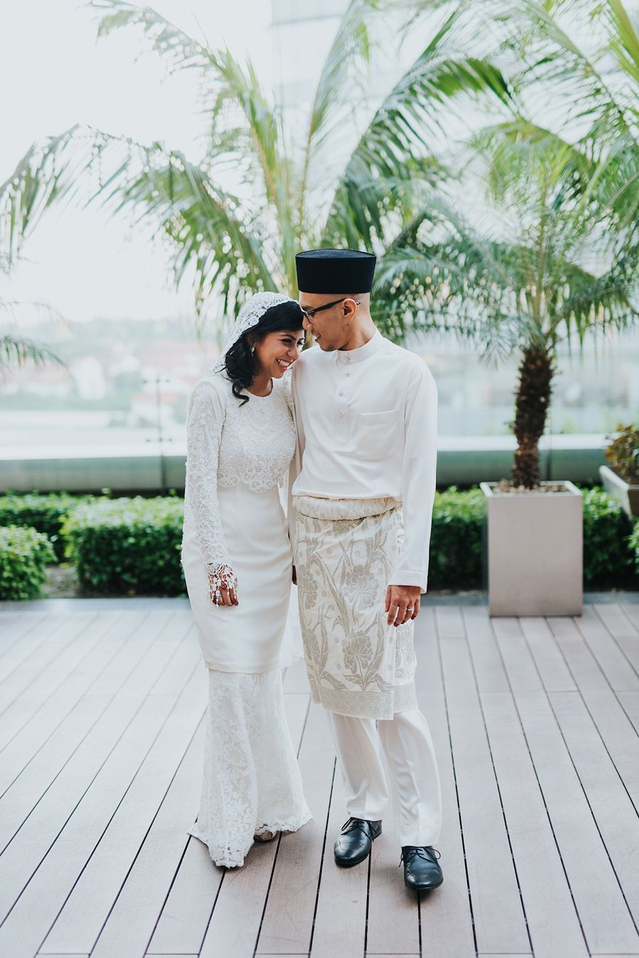 Bride and groom in traditional muslim wedding outfits and pose for
