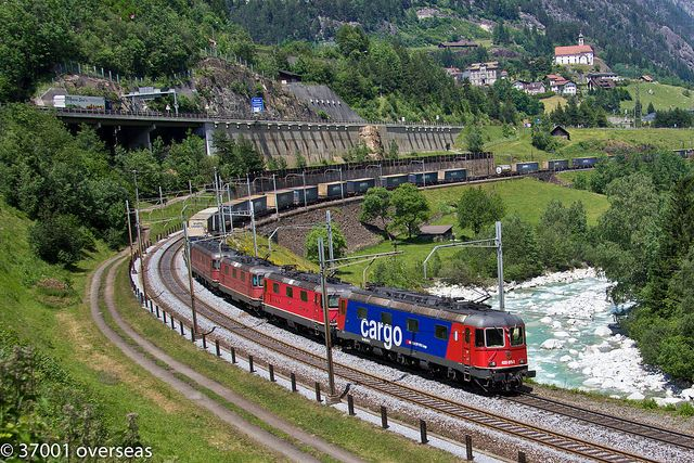 Switserland - Passing the River Reuss are four SBB locos, numbers 620 075 11132 11281 and 11676 and just visible at the rear is banker 11163 rounding Wattinger curve at Wassen low level with an Italian bound intermodal (Norfolk line at front and DSV piggybacks at rear)