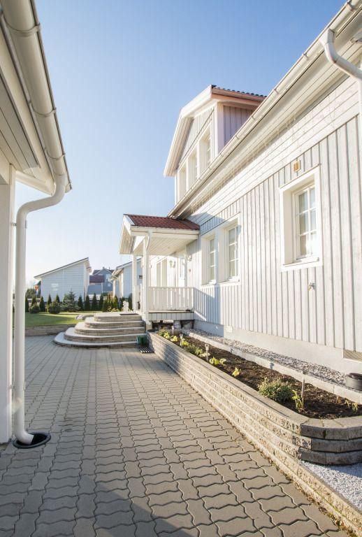 Älvsbytalon Tuulikki-talo kylpee auringossa. Lisävarusteena komea erkkeri.