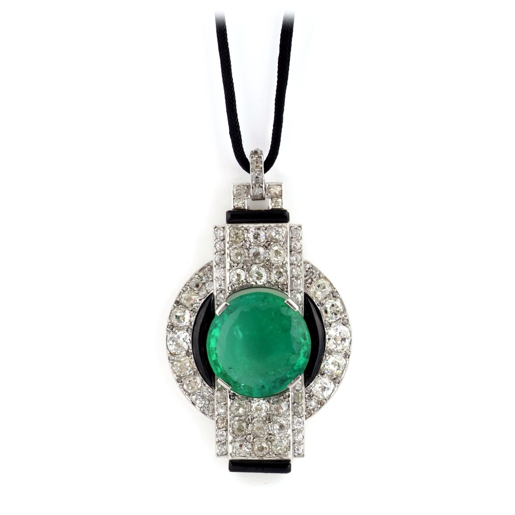 GEORGES FOUQUET. A LACQUER, EMERALD AND DIAMOND BROOCH/PENDANT. Of Modernist design, centring on a circular-cut emerald weighing 13.64 carats, within an annular surround of circular-cut diamonds accented with black lacquer, cut-through with a similarly-set stepped rectangular section, suspended from its original silk cord, later restored brooch fitting, 1924-1930. Accompanied by a photograph courtesy of the Fouquet Archives conserved by the Musée des Arts décoratifs, Paris.