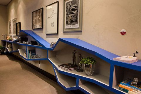 Acompanhando a extensão da parede, a estante suspensa tem altura e profundidade irregulares. Assim, é possível acomodar objetos distintos, como livros, vasos, esculturas e até uma cafeteira. O desenho é de autoria de Adriano Stancati e Daniele Guardini, que assinam o projeto deste Escritório Contemporâneo.